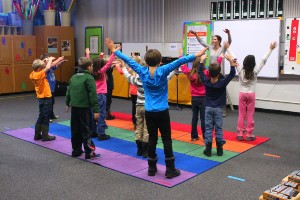 Students doing yogo with teacher on colorful mats