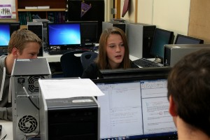 Three high school students working together on classroom computers